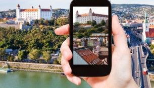 travel concept - tourist snapshot of Bratislava Hrad castle over old town on smartphone