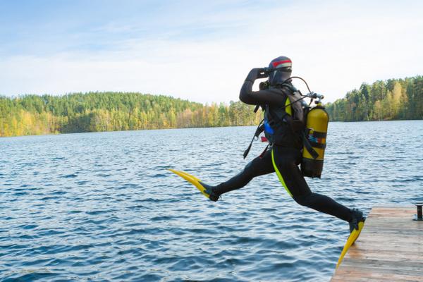 Дайвер прыгает в воду лесного озера