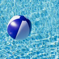 Floating blue and white beachball in swimming pool