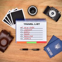 Camera, passport, pen and note pad with drawing travel list. Work desk tourist.