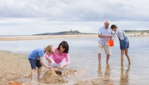 Grandparents and grandchildren are playing together on the beach. They all look happy playing with the sand and water.