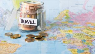 Travel budget concept. Money saved for vacation in glass jar on world map background, copy space. Banknotes and coins for big adventure.