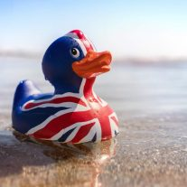 British flag rubber duck in the sea at the beach